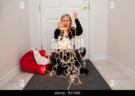 A frustrated woman can't get the christmas lights to untangle so she screams in anger - Stock Image