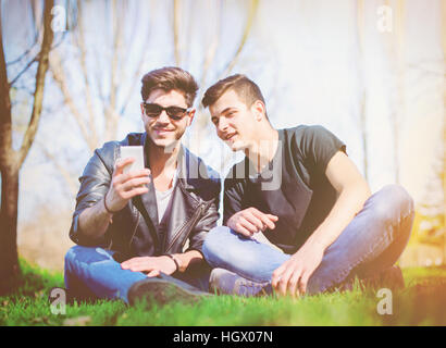 Friends sitting in the park and looking at the cell phone - Stock Image