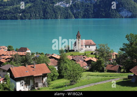Old church and timber chalets in Brienz, Switzerland. Turquoise water of Lake Brienz. - Stock Image