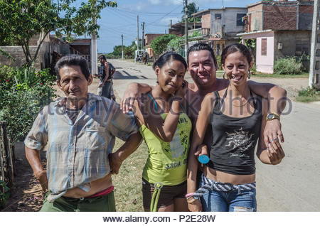 Group of local Cubans – two male and two female – having fun posing for camera in the residential street where they live.  Trinidad, Cuba, November 20 - Stock Image
