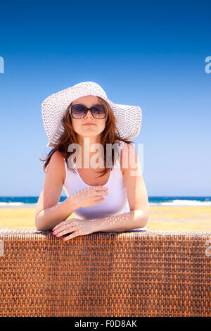 The young beautiful woman in a hat on vacation, on a sunny beach - Stock Image