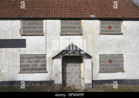 A disused house with bricked up windows and door. - Stock Image