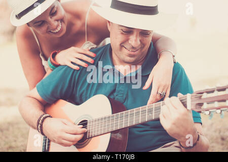 Romantic adult couple in love play together a guitar and enjoy the relationship - cheerful people with music and outdoor leisure activity in vintage c - Stock Image