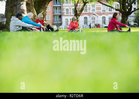 Active seniors stretching in park - Stock Image