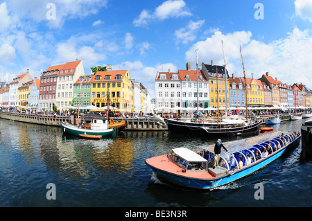Fisheye view on colorful houses and tour boat in famous canal Nyhavn in Copenhagen, Denmark - Stock Image