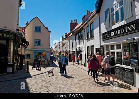 Tourists walking down the cobbled street of Church Street. - Stock Image