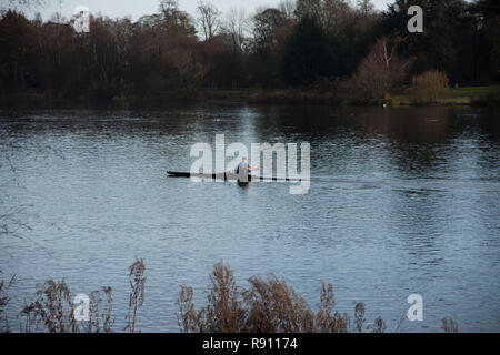 A single person enjoying being out on the lake rowing in his scull boat. - Stock Image