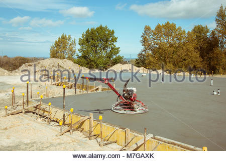Petrol driven trowel on freshly poured concrete floor - Stock Image