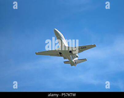 A Portuguese registered Cessna 560XL from Netjets Europe climbs swiftly  out from Inverness Dalcross Airport into a beautiful blue sky. - Stock Image