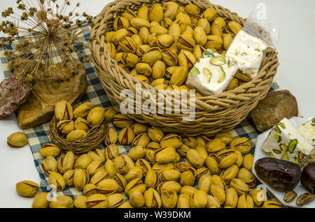 Wicker basket with pistachios and a white plate with dates and nougat, lie among the stones and dry twigs on paper in a blue cage - Stock Image
