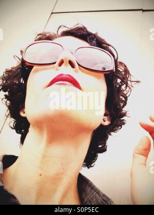 Woman looking up wearing sunglasses and red lipstick ready for business - Stock Image