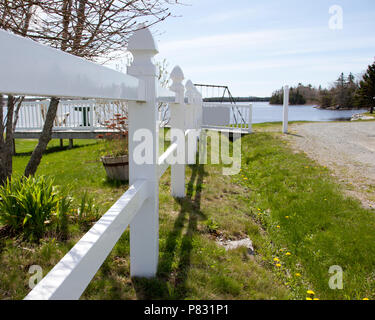 A white picket fence runs along a road down to the beach - Stock Image