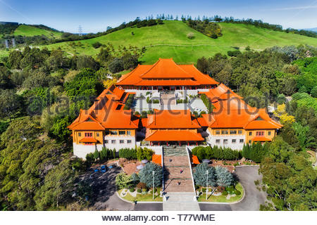 Massive main palace of Nan Tien Buddhist temple in the middle of green Chinese garden on hillside of Australian country near Wollongong. Aerial elevat - Stock Image