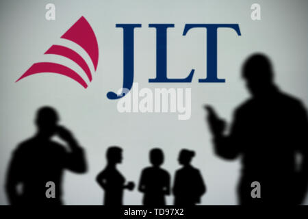 The Jardine Lloyd Thompson logo is seen on an LED screen in the background while a silhouetted person uses a smartphone (Editorial use only) - Stock Image