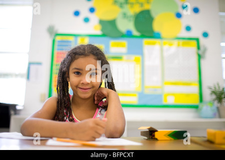 An African American girl in a grade school classroom coloring with crayons. - Stock Image
