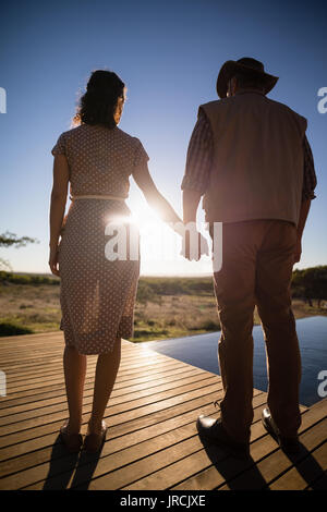 Couple standing with hand in hand during safari vacation - Stock Image