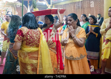 A devout Hindu worshipper (orange) surrounded by her family gives thanks at a service in a temple in Queens, New York City. - Stock Image