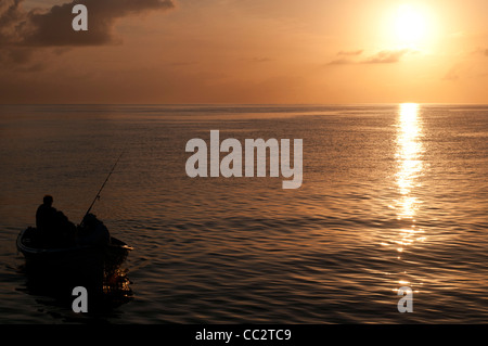 A small boat with fisherman comes in at the end of the day, silhouetted against the setting sun on a calm day on - Stock Image