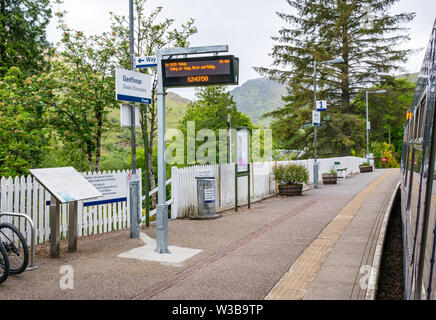 Glenfinnan rural train station platform and name sign with ScotRail train on West Highland railway line, Scottish Highlands, Scotland, UK - Stock Image