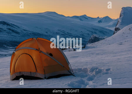 Camping in winter season, Mount Skerfe and Sarek national park in background, sky is colorful of sun setting, Jokkmokk county, Sarek national park, Sw - Stock Image