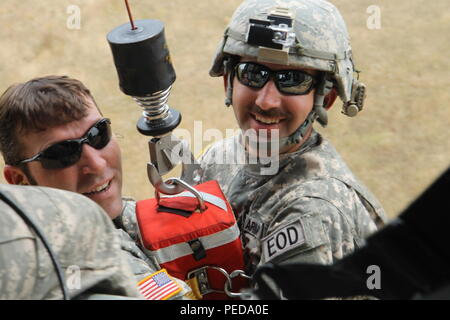 U.S. Army 1st Lt. Christopher Watson and Staff Sgt. Brian Harris, National Guard Soldiers from the 666th Explosive Ordnance Company out of Jacksonville, Ala., and currently assigned to Multinational Battle Group-East, are lifted on a hoist by a UH-60 Black Hawk helicopter during hoist training August 3, 2015, at Camp Bondsteel, Kosovo. The training was conducted to familiarize the EOD team with hoist operations in case medevac assistance is needed while conducting missions for MNBG-E. (U.S. Army photo by Sgt. Erick Yates, Multinational Battle Group-East) - Stock Image