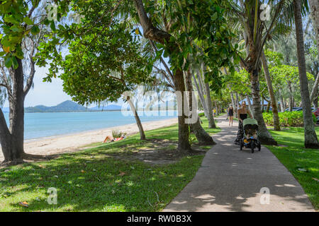 Mother pushing a pram on a walking path under bent palmtrees along the beach, Palm Cove, Far North Queensland, QLD, FNQ, Australia - Stock Image