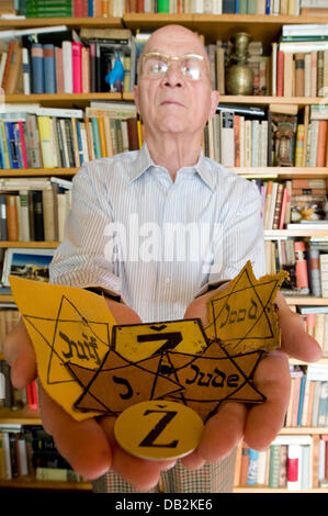 Wolfgang Haney holds yellow badges from various European countries for the camera at his home in Berlin,Germany, - Stock Image
