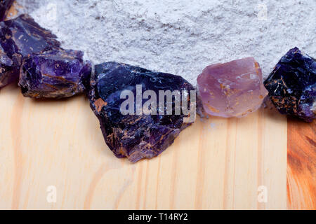 A pile of fluorine spar surrounded by fluorite stones on wood. - Stock Image