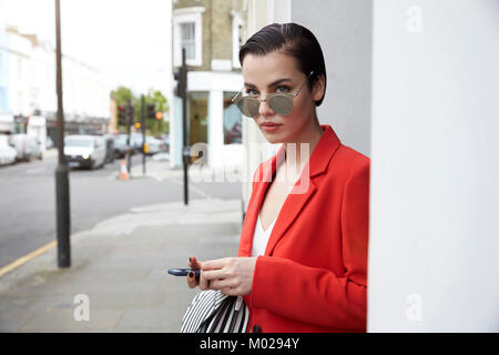 Woman in red jacket on the street, looking over sunglasses - Stock Image