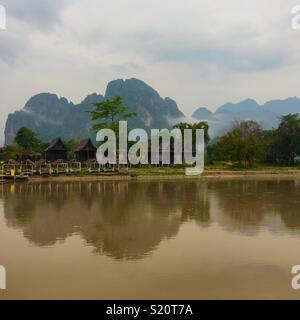 Mountains reflecting on river in Vang Vieng Laos - Stock Image