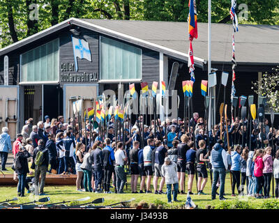 Rowing clubs celebrate the start of the rowing season, holding sculls upright in a circle, meeting in front of club - Stock Image