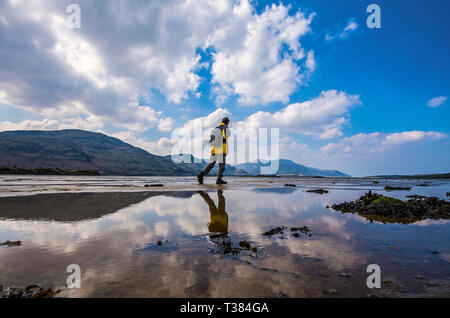 Ardara, County Donegal, Ireland. 7th April 2019. A walker is seen on Ballyganny Strand on a warm afternoon on the north-west coast. Credit: Richard Wayman/Alamy Live News - Stock Image