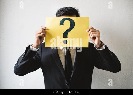 Young adult asian businessman holding yellow signboard paper with QUESTION MARK. Concept of business FAQ and questions - Stock Image