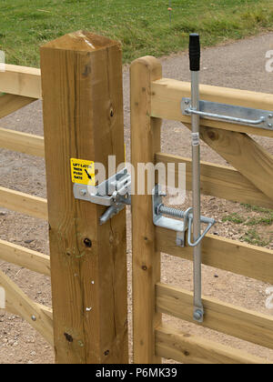 New galvanised metal bridle gate latch furniture fittings on wooden gate on horse bridleway, Derbyshire, UK - Stock Image