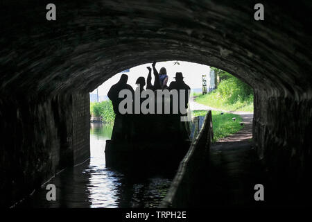 Silhouetted rear view of people on narrow boat on UK canal moving through a dark canal tunnel; upside down man, legs in air, propels boat by legging. - Stock Image