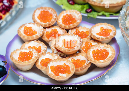 Tartlets with red caviar on a plate. - Stock Image