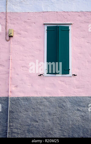 Dark green shutters on a tricolor exterior roughcast wall. Greek island of Tinos. - Stock Image