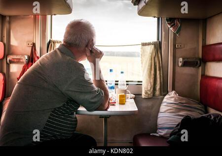 VLADIMIR, RUSSIE, MAI 19: Un voyageur contemple le paysage a travers la vitre de son compartiment a bord du Transsiberien - Stock Image