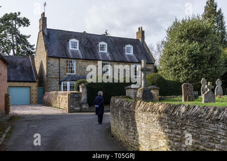 Senior woman walking along a back lane in the village of Collingtree, Northamptonshire, UK; the OLd Rectory to the rear, the churchyard to the left - Stock Image