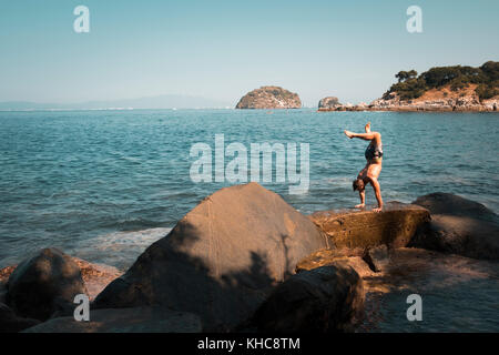 Man does handstand on an ocean front cliff as part of his yoga exercise. Yoga retreat Puerto Vallarta - Mismaloya, - Stock Image