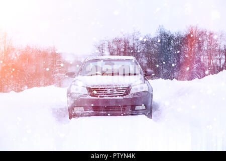 the car stands on a snow-covered road in a wintertime cloudy day - Stock Image