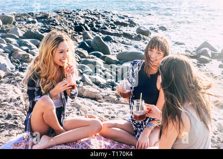 Group of young girls have fun together in friendship on the rocky beach near the ocean for vacation leisure activity - friends people cheerful and bea - Stock Image