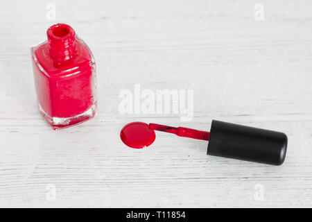 red nail polish bottle on wooden surface spilling color, concept of beauty industry - Stock Image