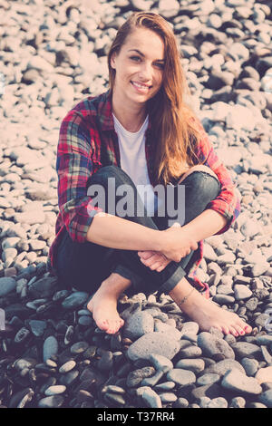 Portrait of young caucasian hipster woman sitting on the rocks in summer sunny day smiling at the camera with happiness - tourist and vacation concept - Stock Image