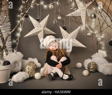 A little girl is sitting in a winter wonderland setip with trees, hanging stars and christmas lights around the - Stock Image