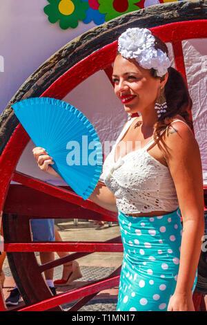 Arroyo de la Miel, Spain - 17th June 2018: Girl with fan wearing a fascinator at a local fiesta. Spain is famous for its fiestas. - Stock Image