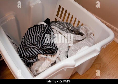 Shorts and underwear in a white laundry basket ready to be washed - Stock Image
