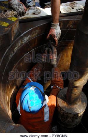 Worker in hole on offshore oil platform - Stock Image