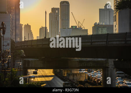 BANGKOK, THAILAND - NOVEMBER 2018: Orange sunset over the street of Bangkok and the skytrain railroad, Thailand - Stock Image