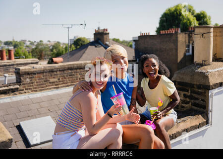 Portrait happy, confident young women friends drinking on sunny summer rooftop - Stock Image